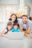 Portrait of smiling family with laptop on table Stock Photography