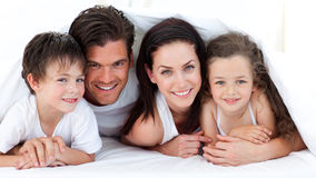 Portrait of a smiling family lying on bed. In parent's bedroom Stock Photos