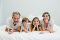 Portrait of smiling family lying on bed in bedroom. At home Stock Images