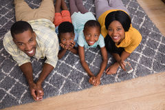 Portrait of smiling family lying on rug at home Stock Photo