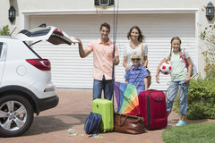 Portrait of smiling family packing car in sunny driveway Stock Photography