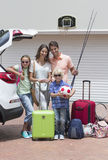 Portrait of smiling family packing car in sunny driveway stock image