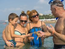 Portrait smiling family playing with the crab in the sea, ocean. Positive human emotions, feelings, joy. Funny cute child making v Royalty Free Stock Photos