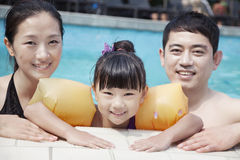 Portrait of smiling family in the pool by the edge looking at camera Royalty Free Stock Photos