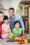 Portrait of smiling family preparing salad Royalty Free Stock Photos