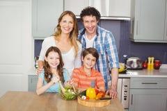Portrait of smiling family preparing vegetable salad. In kitchen stock image