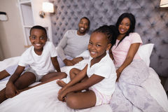 Portrait of smiling family sitting on bed royalty free stock image