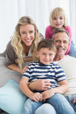Portrait of a smiling family sitting on sofa Stock Images