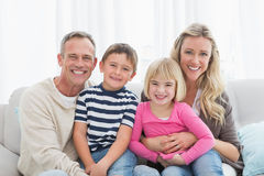 Portrait of a smiling family sitting on sofa Stock Photo