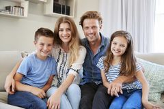 Portrait Of Smiling Family Sitting On Sofa At Home Together royalty free stock photos