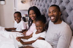 Portrait of smiling family sitting together on bed Stock Images