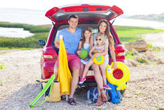 Portrait of a smiling family with two children at beach by car Stock Images