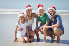 Portrait of smiling family wearing Santa hat at beach. During sunny day Stock Image