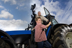Portrait of smiling farmer and grandson leaning out of tractor Stock Photos