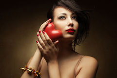 Portrait of smiling fashionable model holding red heart Royalty Free Stock Images