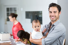 Portrait of smiling father carrying baby at home Stock Image