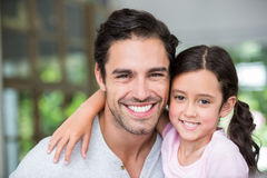 Portrait of smiling father and daughter with arm around Stock Photos