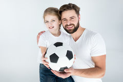 Portrait of smiling father and daughter holding soccer ball Stock Image