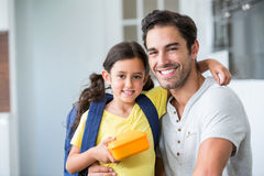 Portrait of smiling father and daughter with lunch box stock image