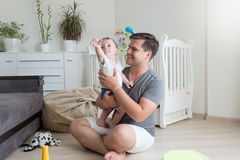 Portrait of smiling father having fun with his baby floor on flo. Portrait of young smiling father having fun with his baby floor on floor at bedroom Royalty Free Stock Image