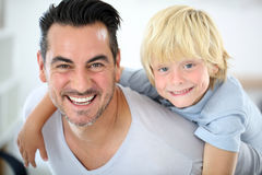 Portrait of smiling father and his boy on his back Stock Image