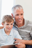 Portrait of a smiling father and his son using a tablet computer Stock Photo