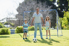 Portrait of smiling father playing football with his son and daughter. At the park Royalty Free Stock Photography
