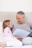 Portrait of a smiling father reading a story to his daughter Royalty Free Stock Photos