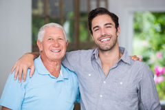 Portrait of smiling father and son with arm around. Wile standing at home Royalty Free Stock Image