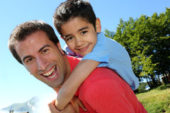 Portrait of smiling father with son on his back. Portrait of father and son having fun in the mountain Royalty Free Stock Image