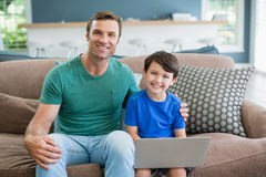 Portrait of smiling father and son sitting on sofa using laptop. In living room at home Stock Images