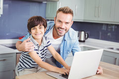 Portrait of smiling father and son using laptop. On table at home royalty free stock photos