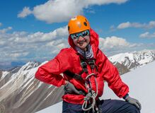 Portrait of smiling female alpinist in helmet in the high mountains