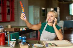 Joyful Creative Woman Speaking by Phone in Workshop. Portrait of smiling female artist looking at color swatches and speaking by phone while choosing palette for Royalty Free Stock Image