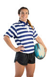 Portrait of smiling female athlete with hand on hip holding rugby ball. Against white background stock photography