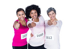 Portrait of smiling female athletes with thumbs up. While standing against white background Royalty Free Stock Photography
