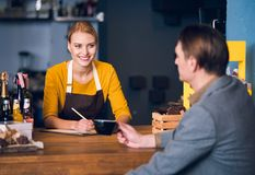 Cheerful woman speaking with client. Portrait of smiling female barista telling with men while writing information in clipboard at table in confectionary shop Stock Photography