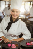 Portrait of smiling female chef finishing dessert plates Royalty Free Stock Images