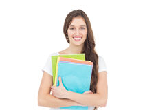 Portrait of smiling female college student holding books Stock Photos