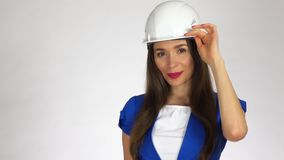 Portrait of smiling female construction engineer or architect in white hard hat against light background Royalty Free Stock Photos