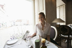 Portrait of smiling female customer sitting at restaurant table Stock Images