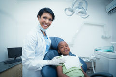 Portrait of smiling female dentist examining boys teeth Royalty Free Stock Photo