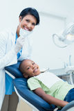 Portrait of smiling female dentist examining boys teeth Royalty Free Stock Images