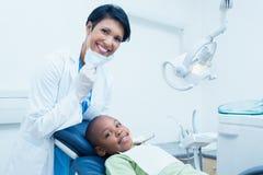 Portrait of smiling female dentist examining boys teeth Royalty Free Stock Photos