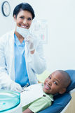 Portrait of smiling female dentist examining boys teeth Royalty Free Stock Image