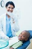 Portrait of smiling female dentist examining boys teeth Royalty Free Stock Image