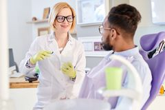Female Dentist Explaining Hygiene Rules. Portrait of smiling female dentist holding toothbrush explaining hygiene rules to patient sitting in dental chair in Stock Images