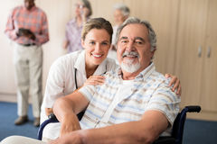 Portrait of smiling female doctor with disabled senior man sitting on wheelchair Stock Photography