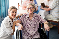 Portrait of smiling female doctor with disabled senior woman sitting on wheelchair