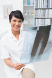 Portrait of a smiling female doctor examining x-ray Royalty Free Stock Photo